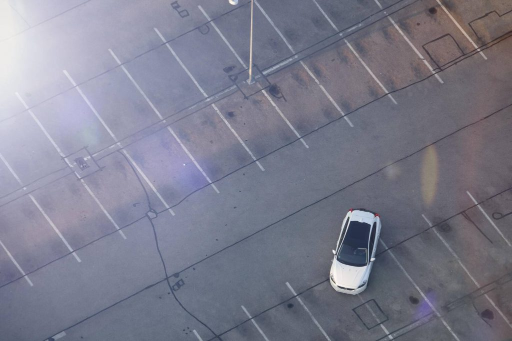 Electric car on parking lot, drone photography - MMAF00092