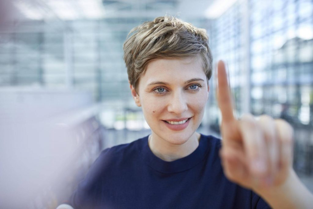 Portrait of blond businesswoman touching at glass pane - PNEF00702