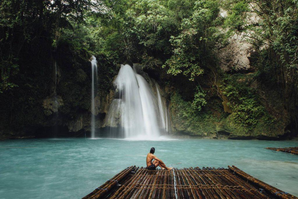 Shirtless man sitting on floating platform over lake at forest - CAVF56472