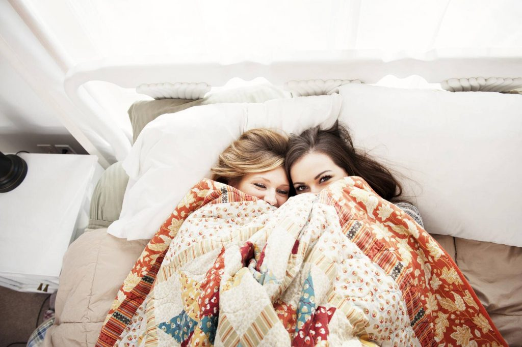 Overhead view of female friends pepping through blanket while lying on bed at home - CAVF00763