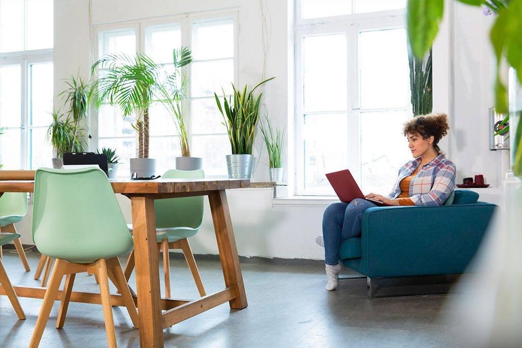 Woman using laptop in armchair in office - FKF03372