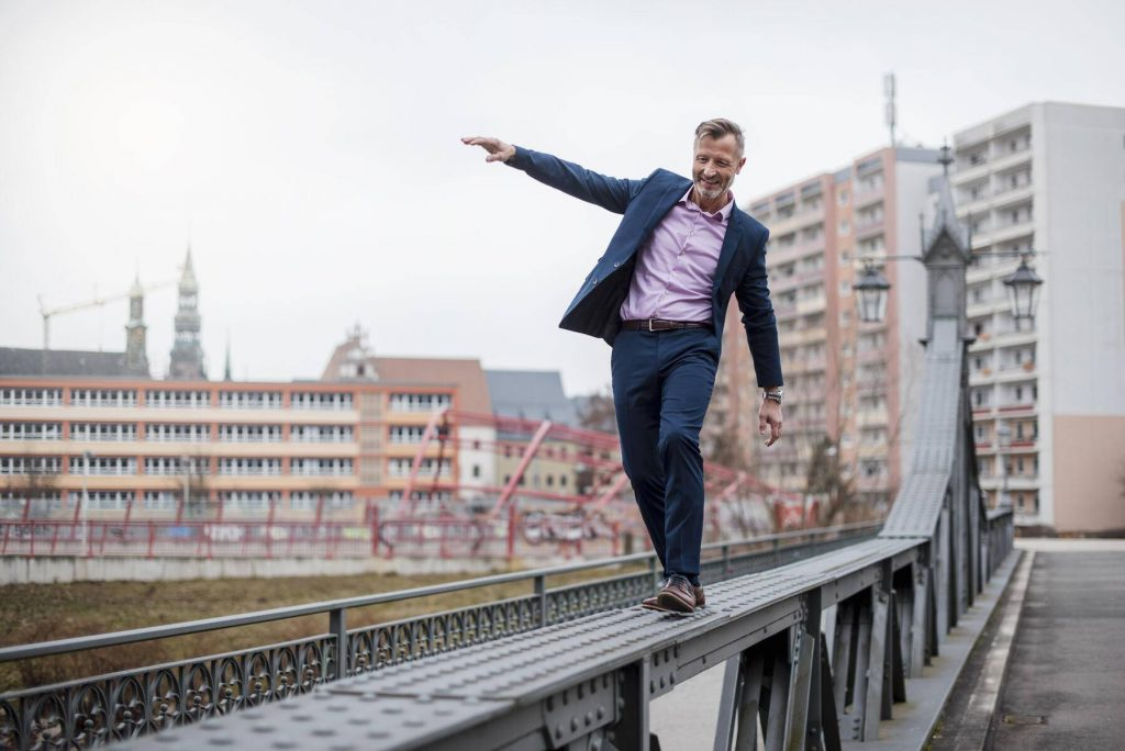 Stylish mature businessman wearing blue suit balancing on railing of bridge - DIGF03279