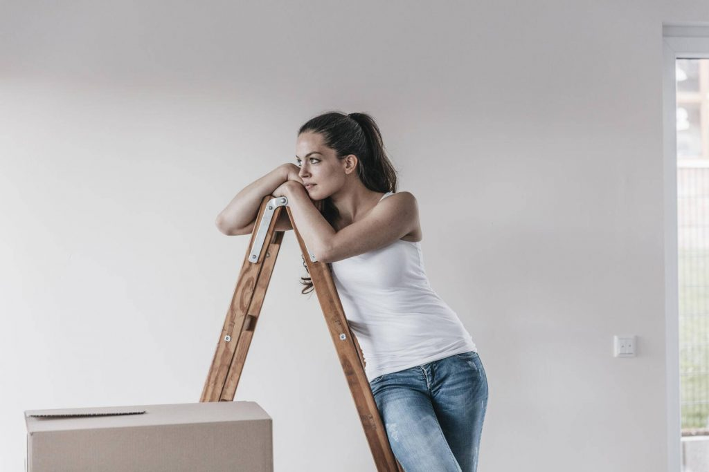 Mature woman standing in her new home, leaning on ladder - JOSF00560
