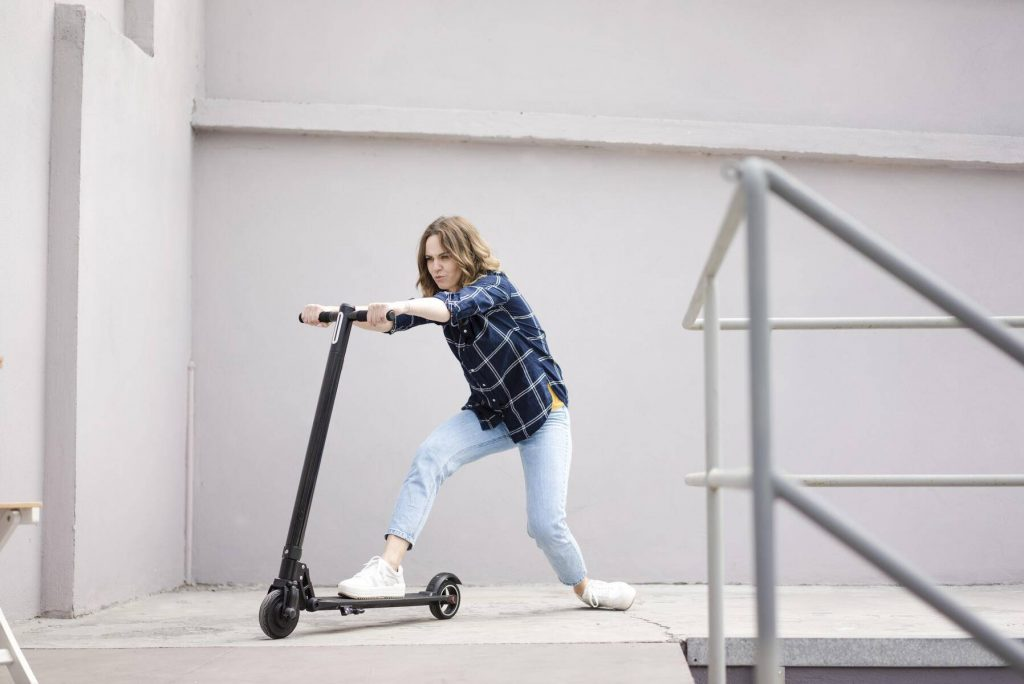 Young woman with electric scooter in a loft - JOSF03359