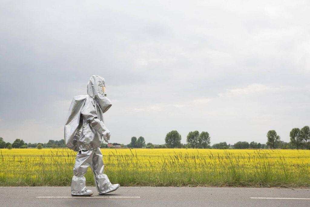 A person in a radiation protective suit walking alongside an oilseed rape field - FSIF00933