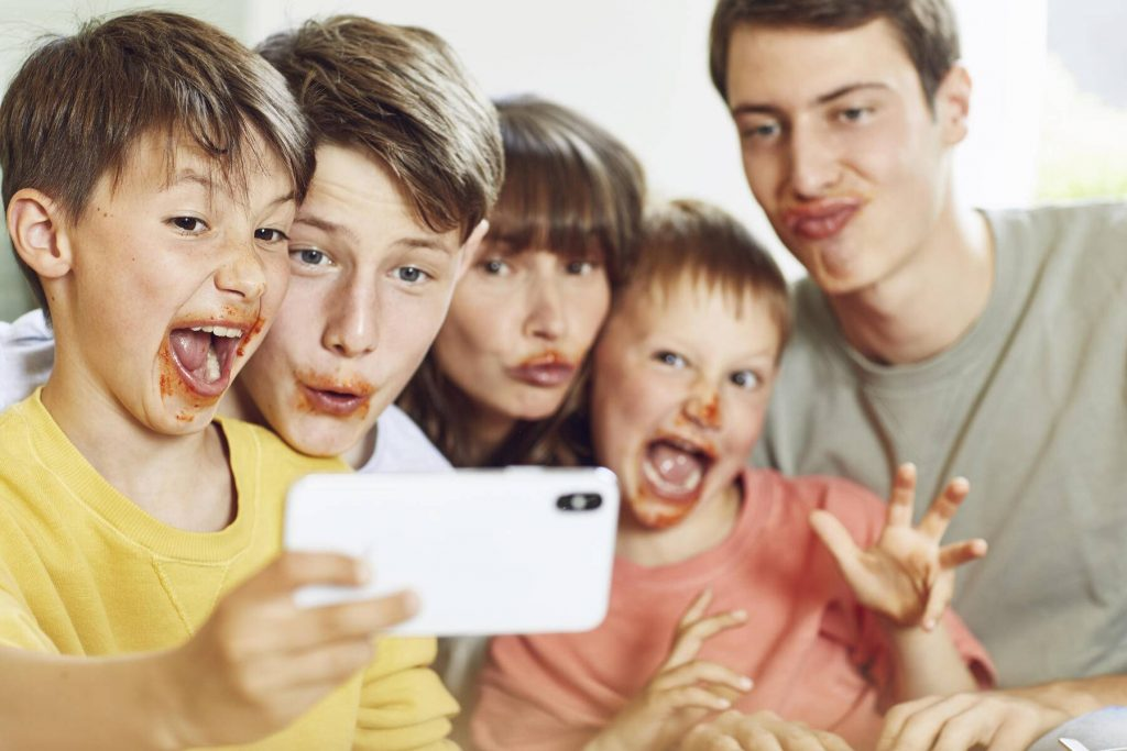 Mother and her four sons taking smartphone selfies at lunch, with faces full of tomato sauce - MCF00176