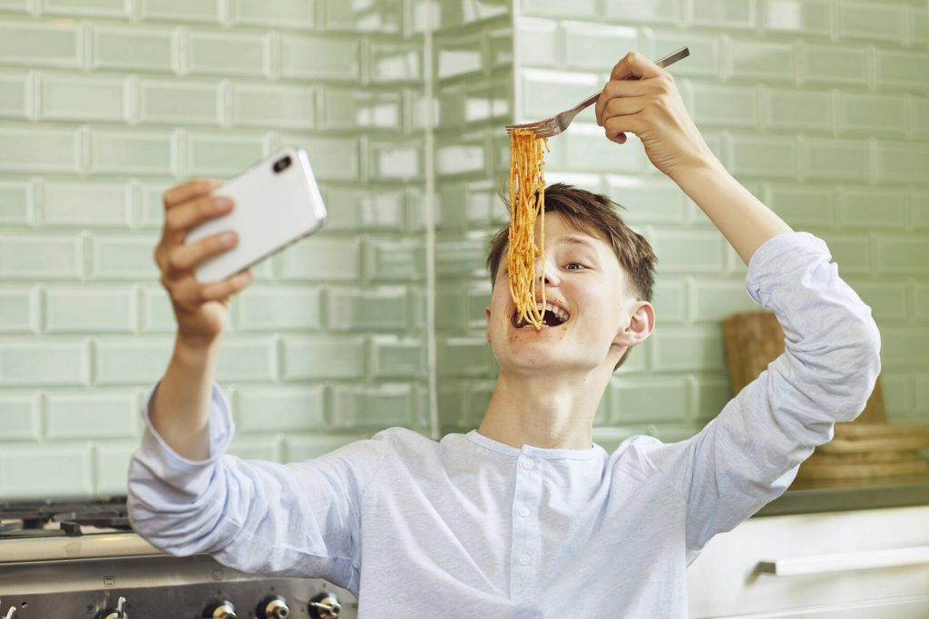 Laughing boy taking smartphone selfie, eating spaghetti - MCF00183