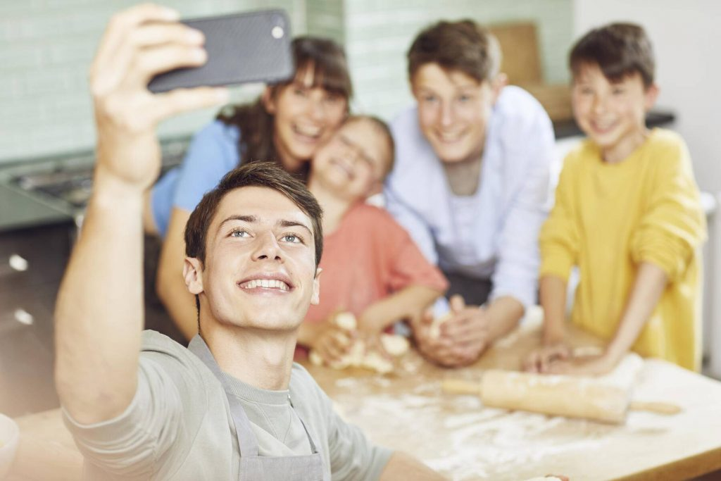 Sone taking pictures of his mother and brothers, preparing pizza at home - MCF00198