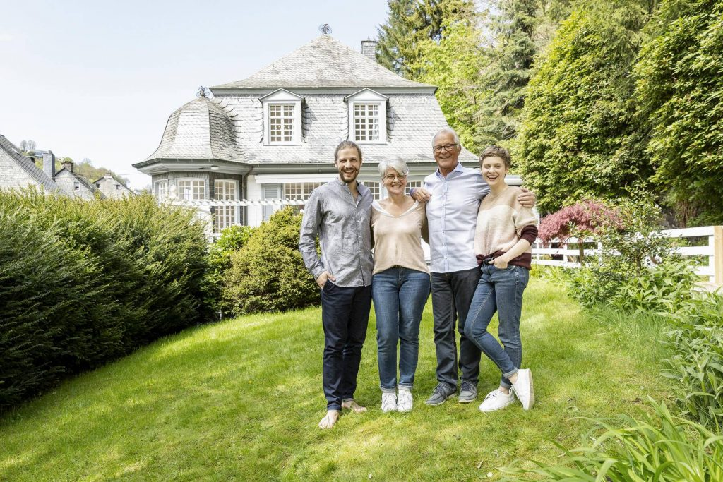 Happy senior couple with adult children standing in garden of their home - MJFKF00126