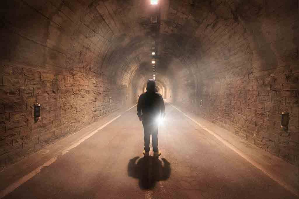 Spain, Huesca, young man exploring a dark tunnel - DHCF00164