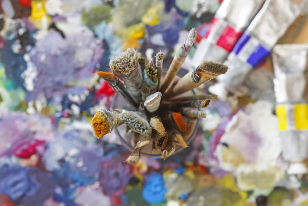 Glass with paintbrushes on artist's palette - JTF000672