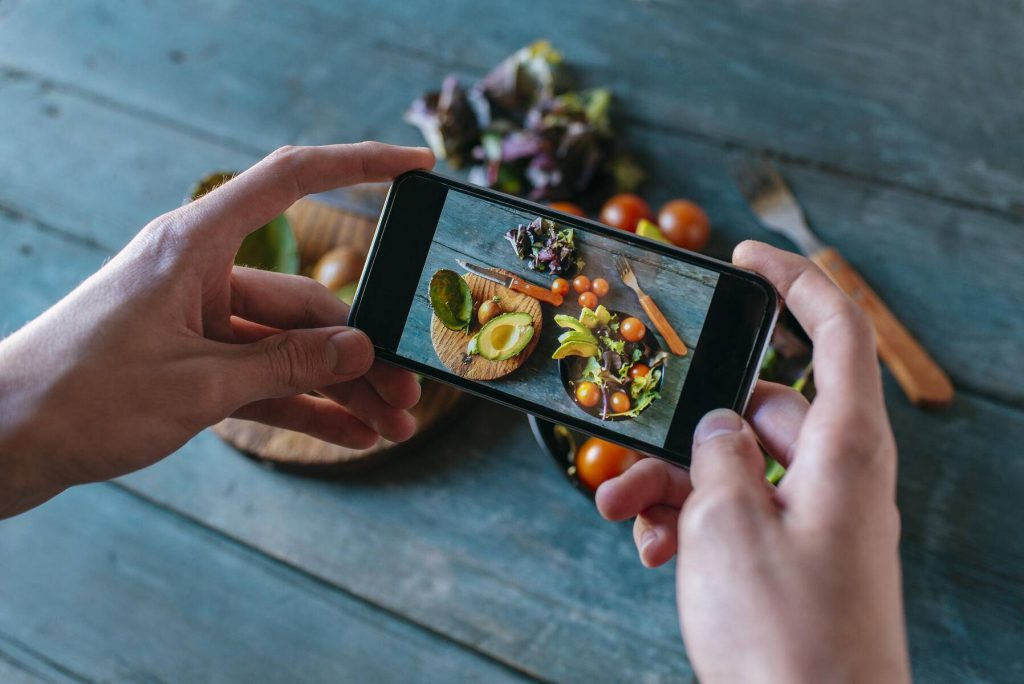 Close-up of man's hands taking picture of avocado salad with smartphone - KIJF01417