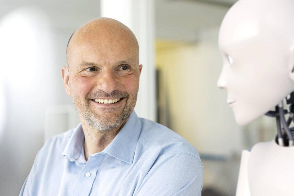 Portrait of smiling businessman looking at robot - KSHSF00003