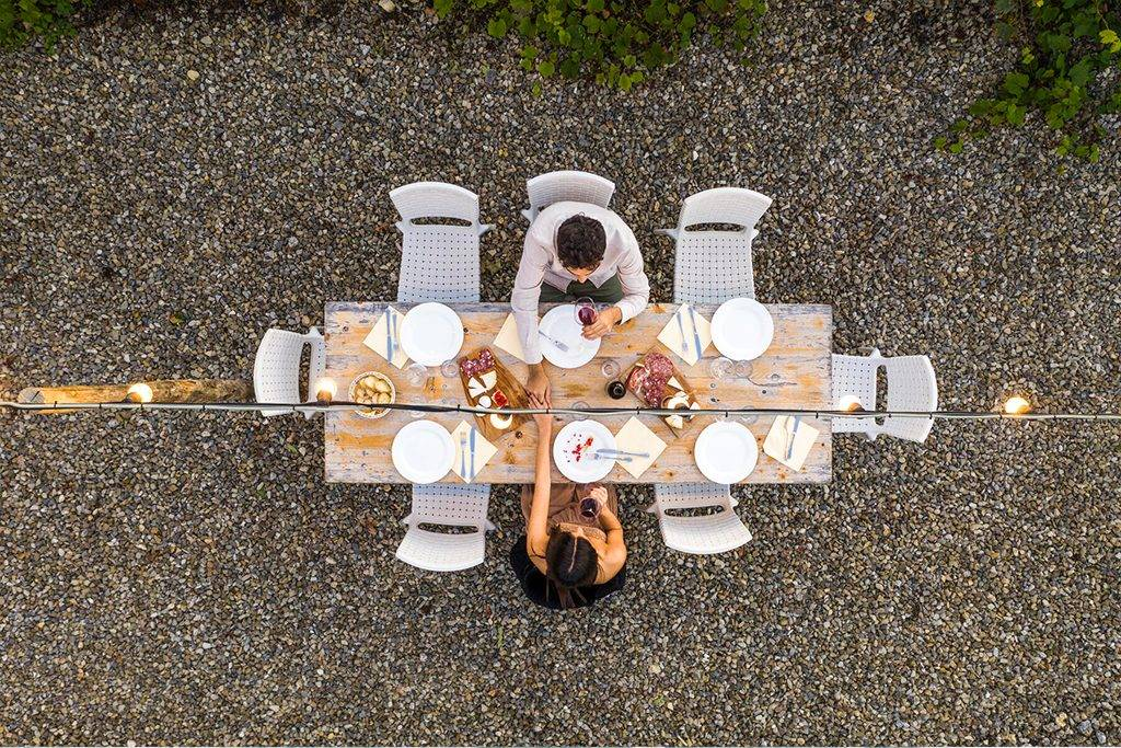 Italy, Tuscany, Siena, top view of young couple dining al fresco holding hands - FBAF00186