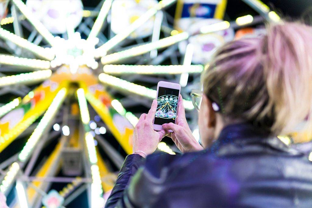 Back view of woman taking photo of big wheel with smartphone at fair   - FBAF00172
