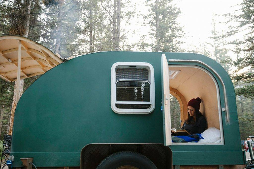 Woman relaxing, reading book in camper van - HEROF39707