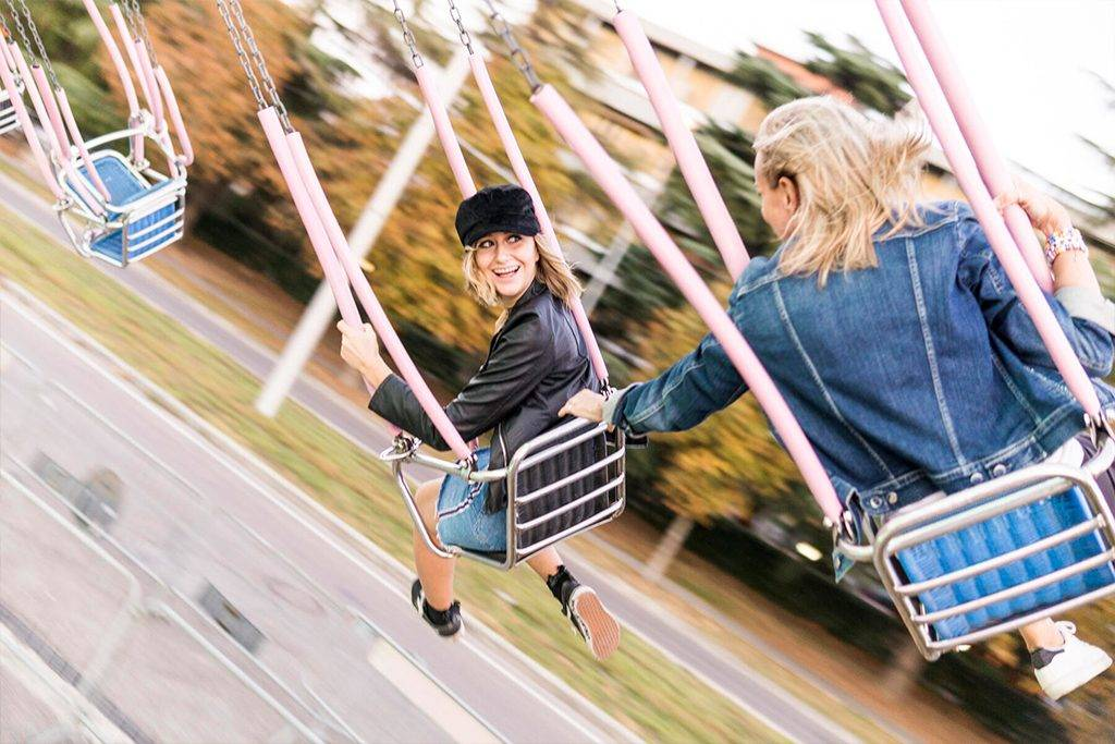Mother and daughter having fun on chairoplane  - FBAF00166