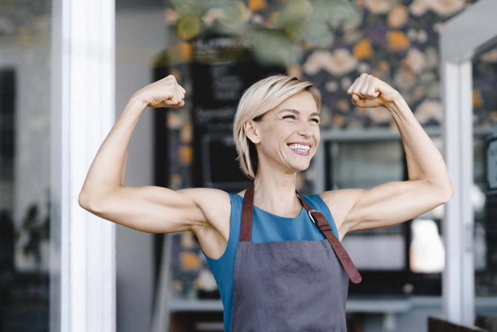 Proud business owner flexing muscles, laughing