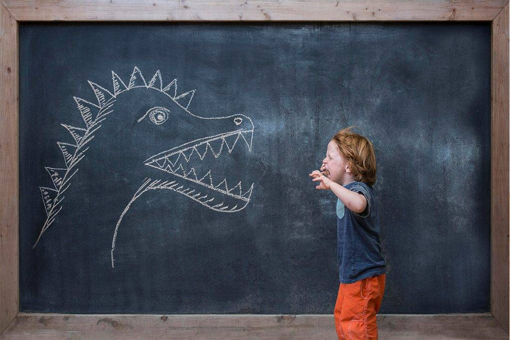 Young boy roaring at dinosaur drawing on blackboard - ISF12167