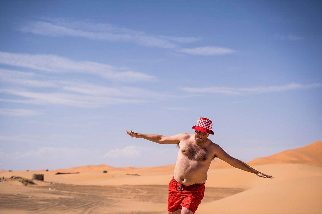 Happy overweight man with swimming shorts running in the desert of Morocco - OCMF00788