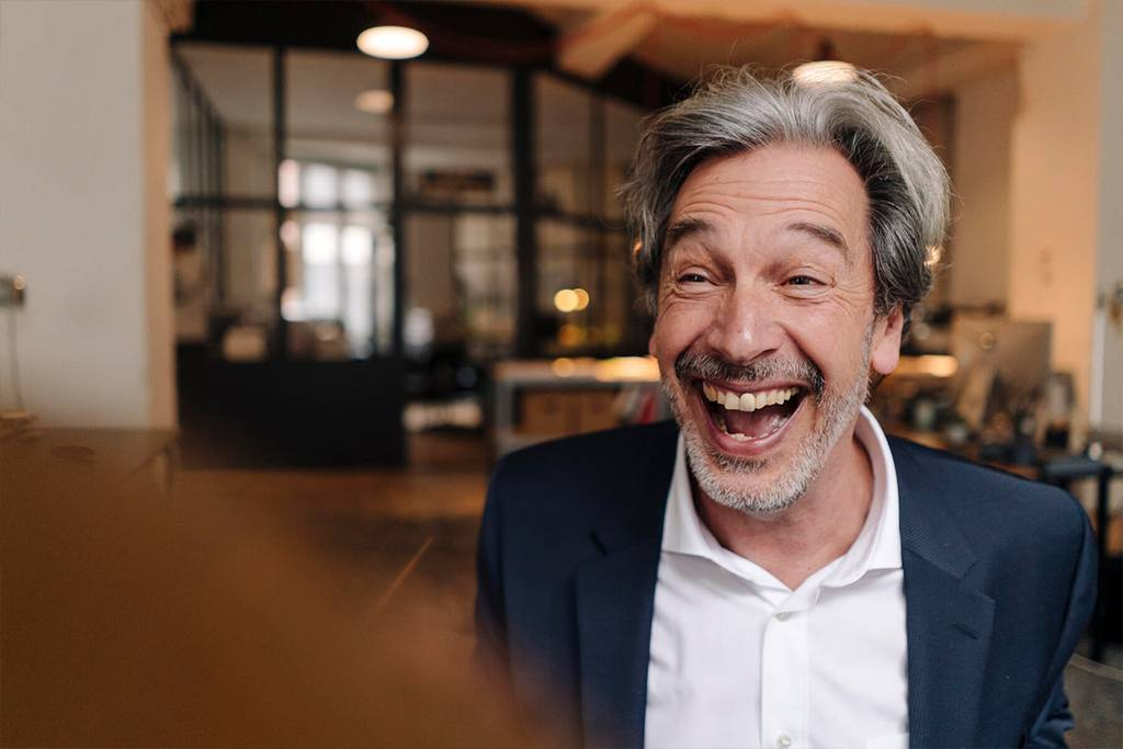 Portait of laughing senior businessman in office - GUSF02815