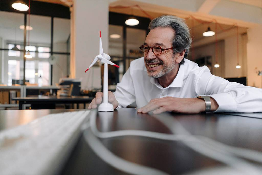 Happy senior businessman with wind turbine model in office - GUSF02938
