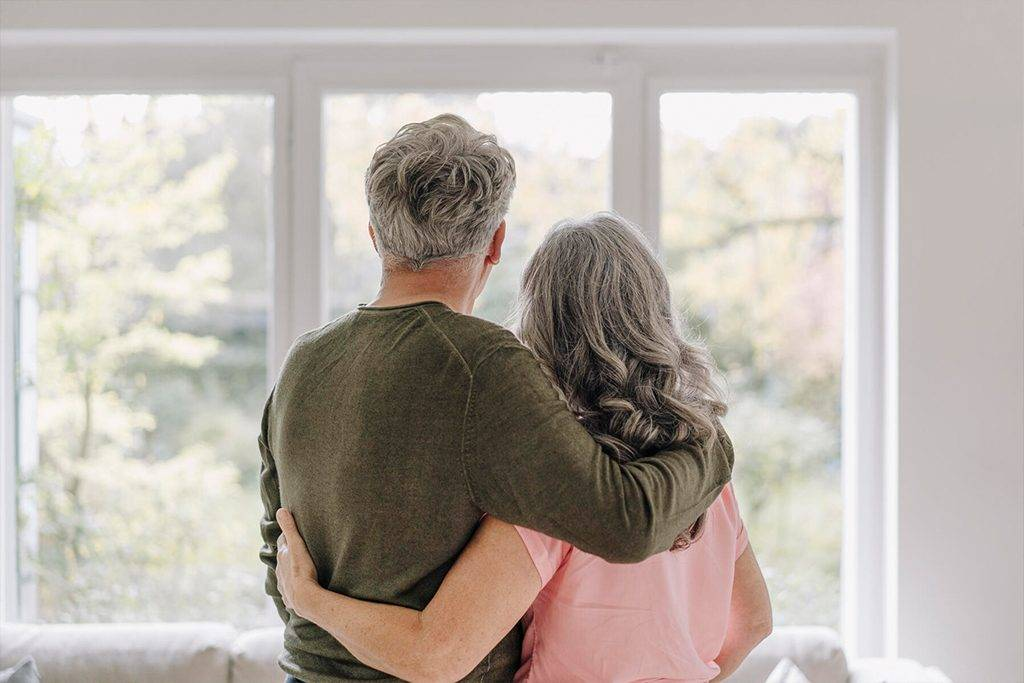Rear view of senior couple looking out of window at home - GUSF03047