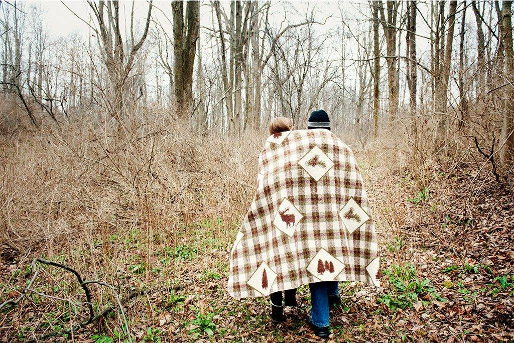 Rear view of couple wrapped in blanket while walking in forest - CAVF00748