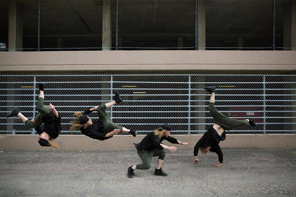 Young man doing parkour cartwheel in urban alley - HEROF31790
