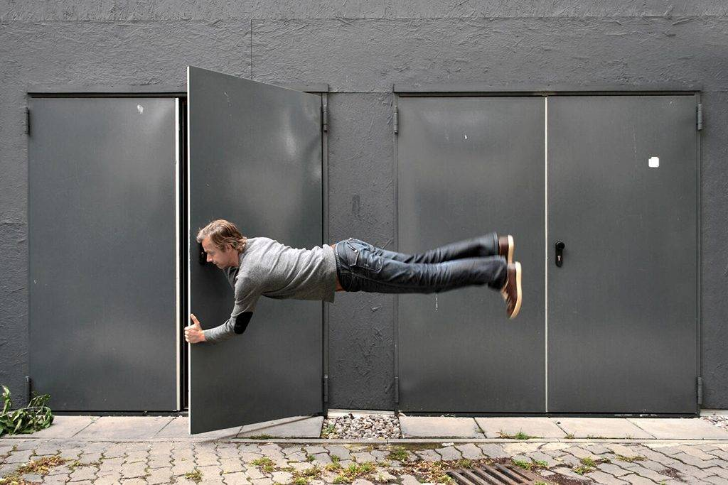 Surreal view of a man balancing off a silver door - INGF03578