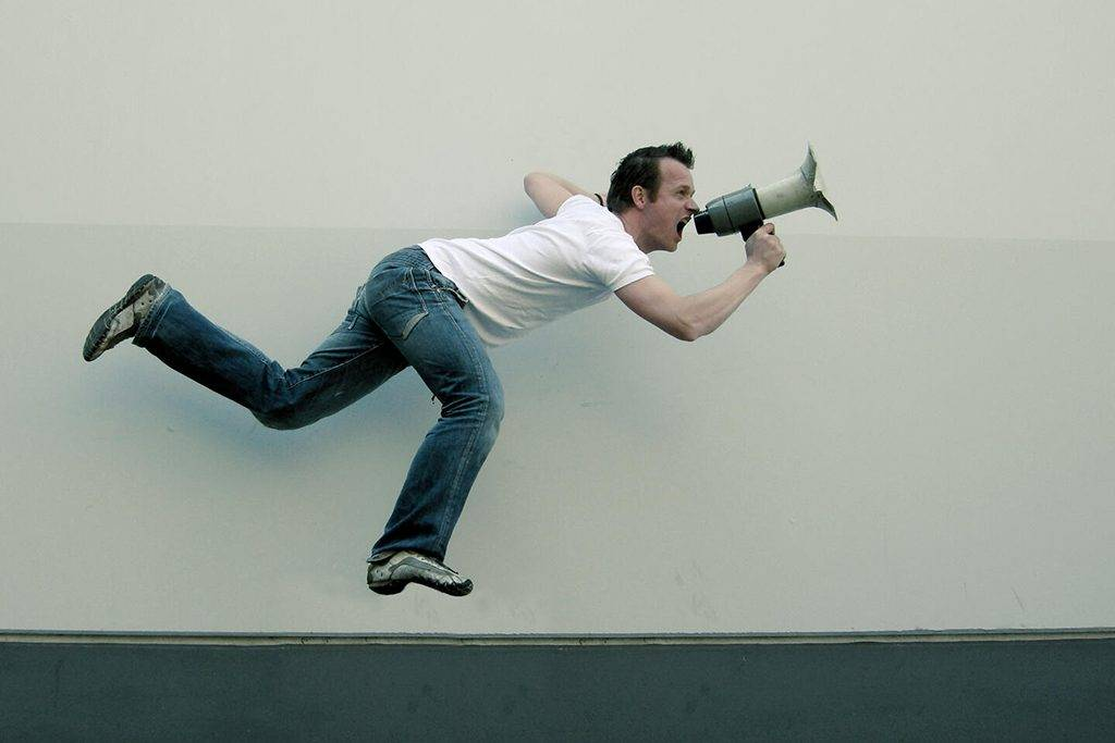 INGF08275 - Action shot of a man in casual clothing in mid air with a megaphone