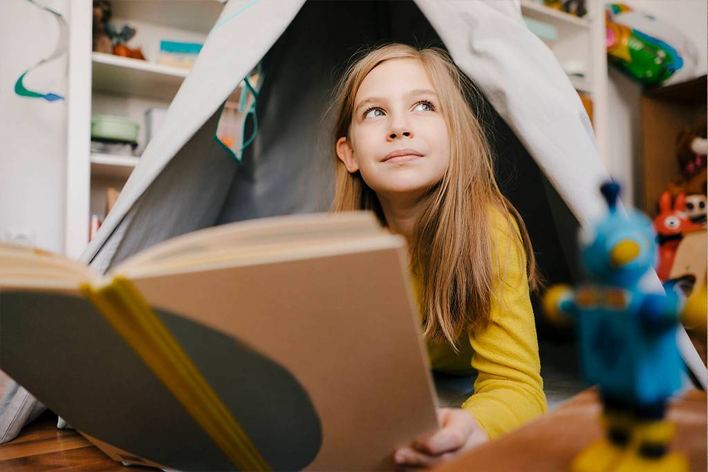 Girl at home reading book in children's room - KNSF05843