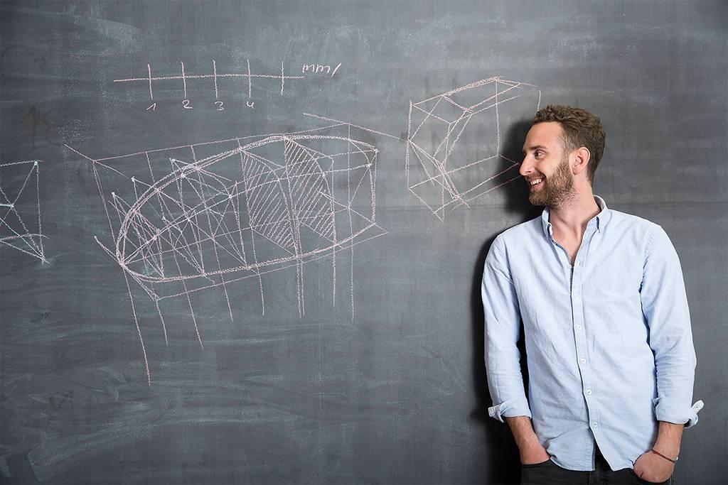 Young man looking at drawing at blackboard - FKF001280
