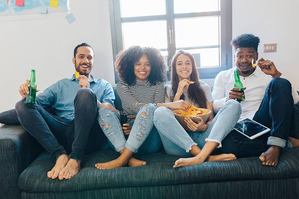 Portrait of happy friends sitting on the sofa - GIOF02787