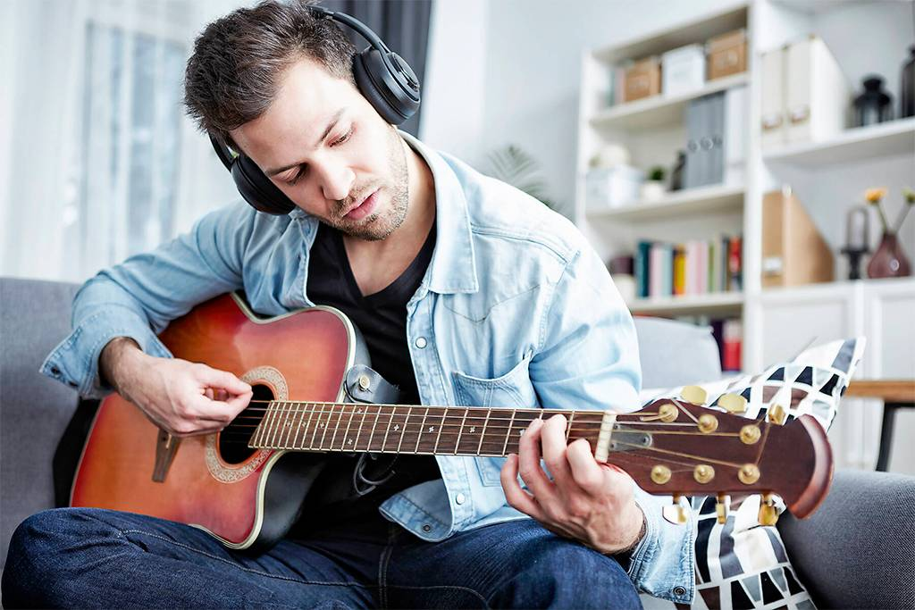 Young man at home sitting on couch wearing headphones and playing guitar - SEGF000454