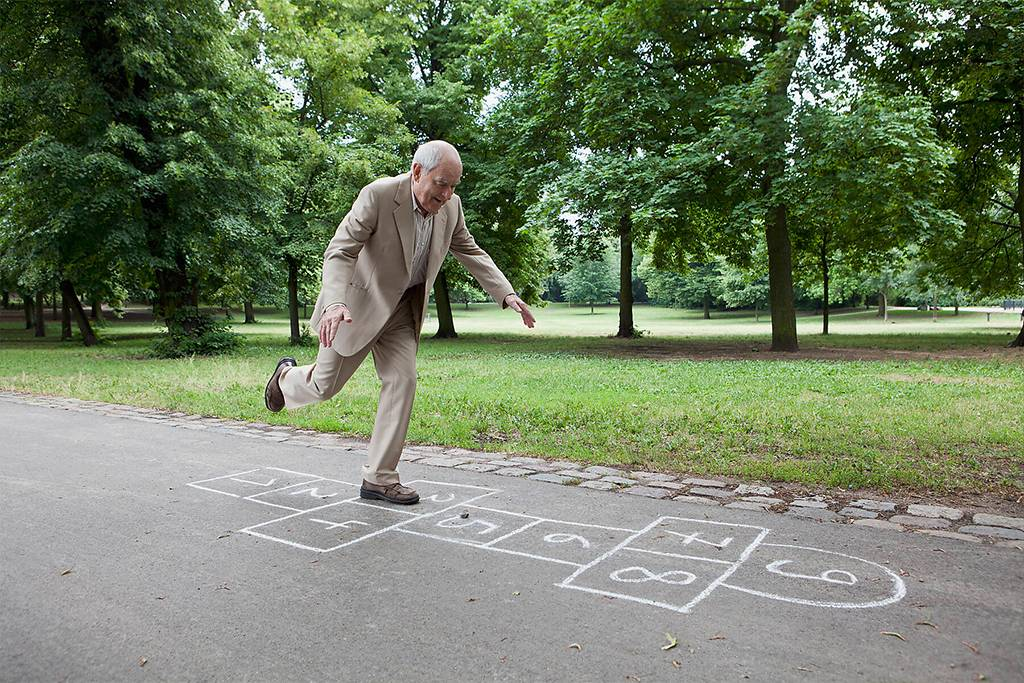 Senior man playing hopscotch in the park - FSIF02882