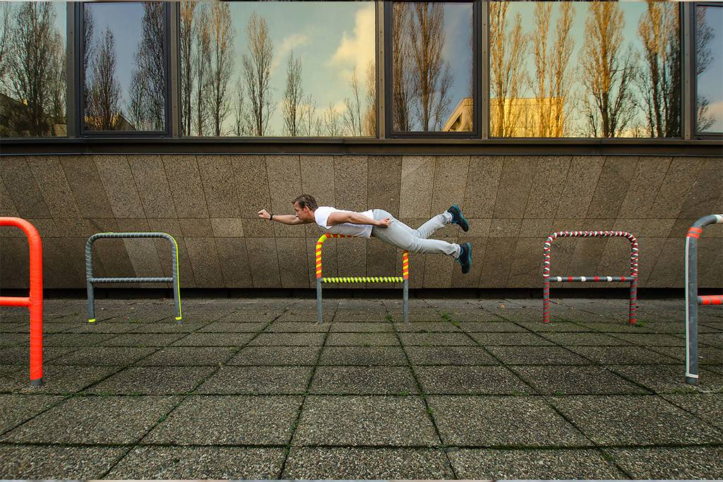 INGF01334  - A man planking outside with the trees reflecting in the background windows