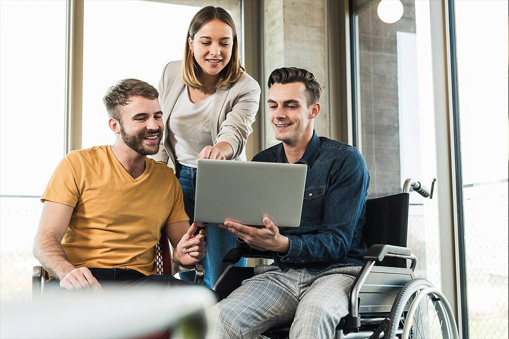 UUF19887 - Young businessman in wheelchair showing laptop to colleagues in office