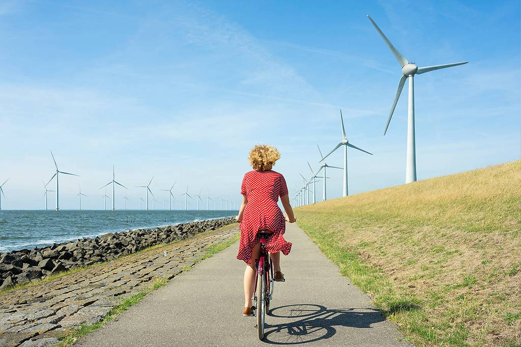 CUF45377  - Girl cycling between onshore and offshore wind farm, Urk, Flevoland, Netherlands