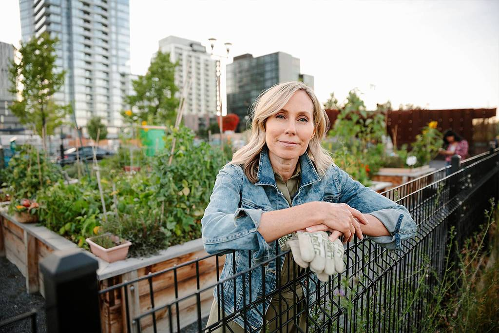HEROF39317 - Portrait confident mature woman at fence in urban community garden