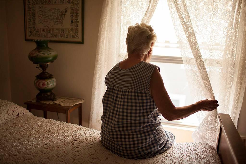 Pensive older woman looking out bedroom window - BLEF05656