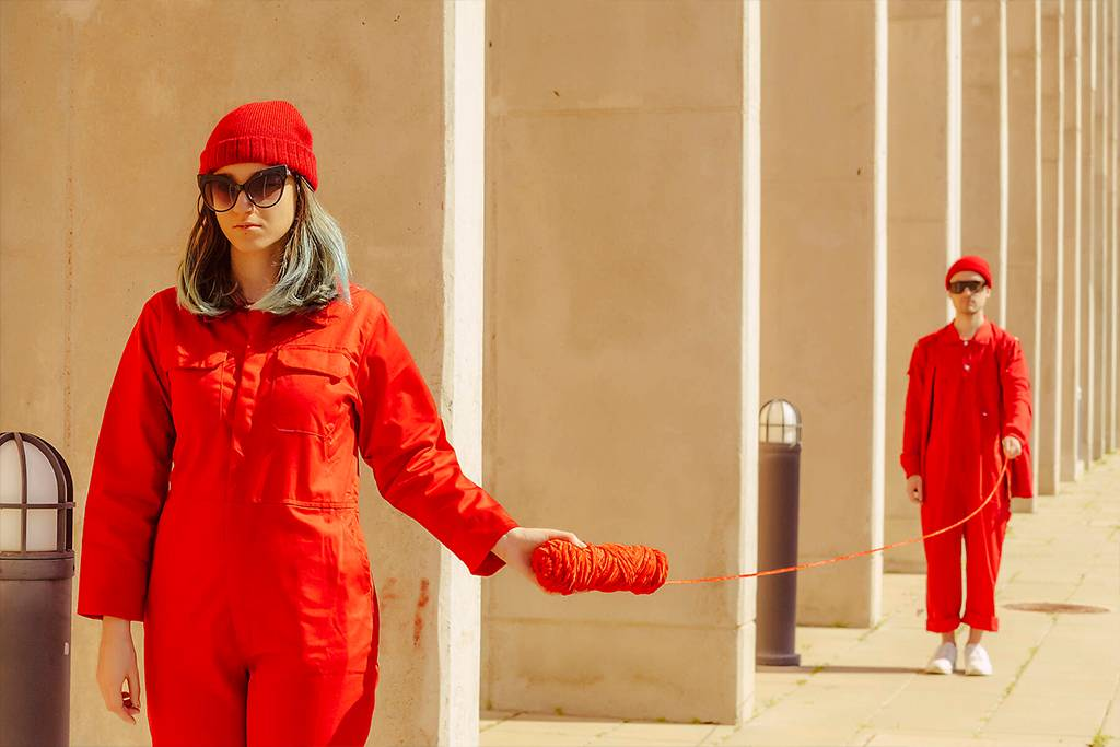 Young couple wearing red overalls and hats standing in a row connected with red string