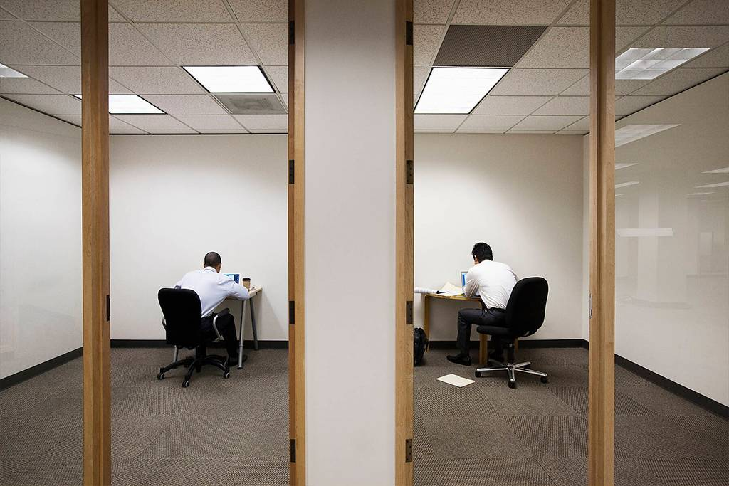 A view of two businessmen working on opposite sides of a wall in two different office spaces - MINF09546