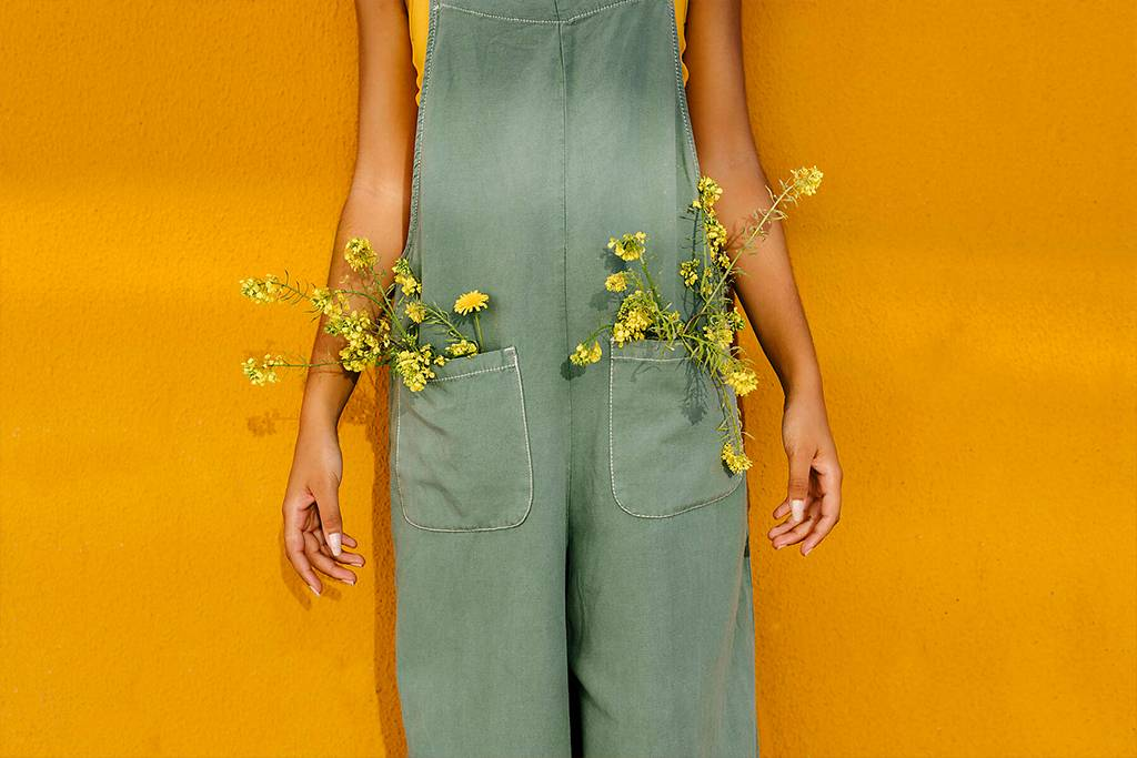 TCEF00473  - Midsection of woman wearing overalls with yellow flowers in pockets