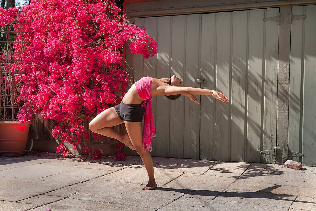 Woman practicing yoga near flowers and fence - BLEF06493