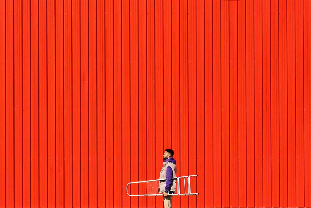 Young man carrying a ladder in front of a red wall - ERRF02821