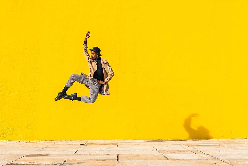Young man dancing in front of yellow wall, jumping mid air - AFVF04545