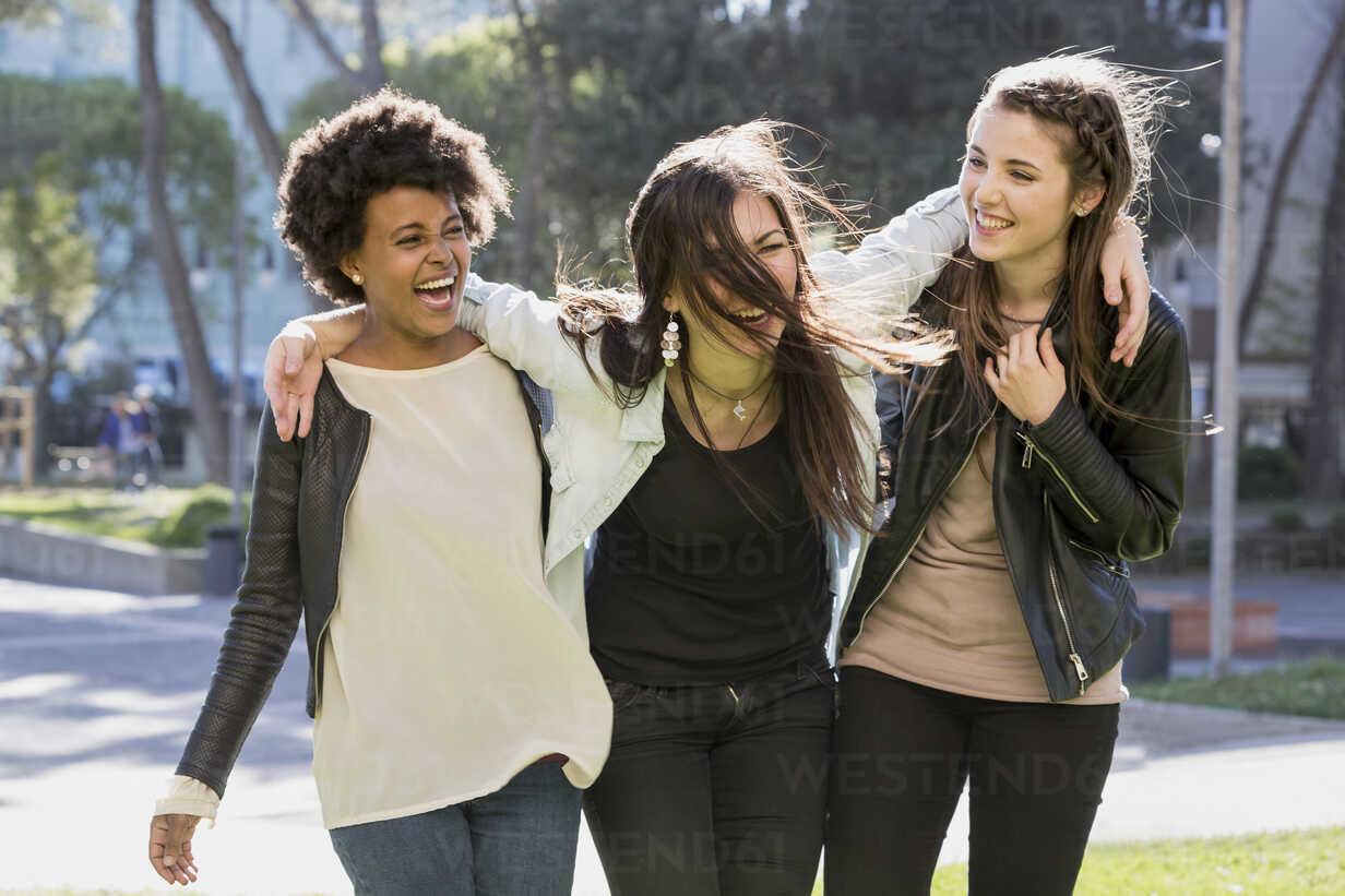 Drei junge Frauen gehen Arm in Arm auf der Straße - Stockfoto