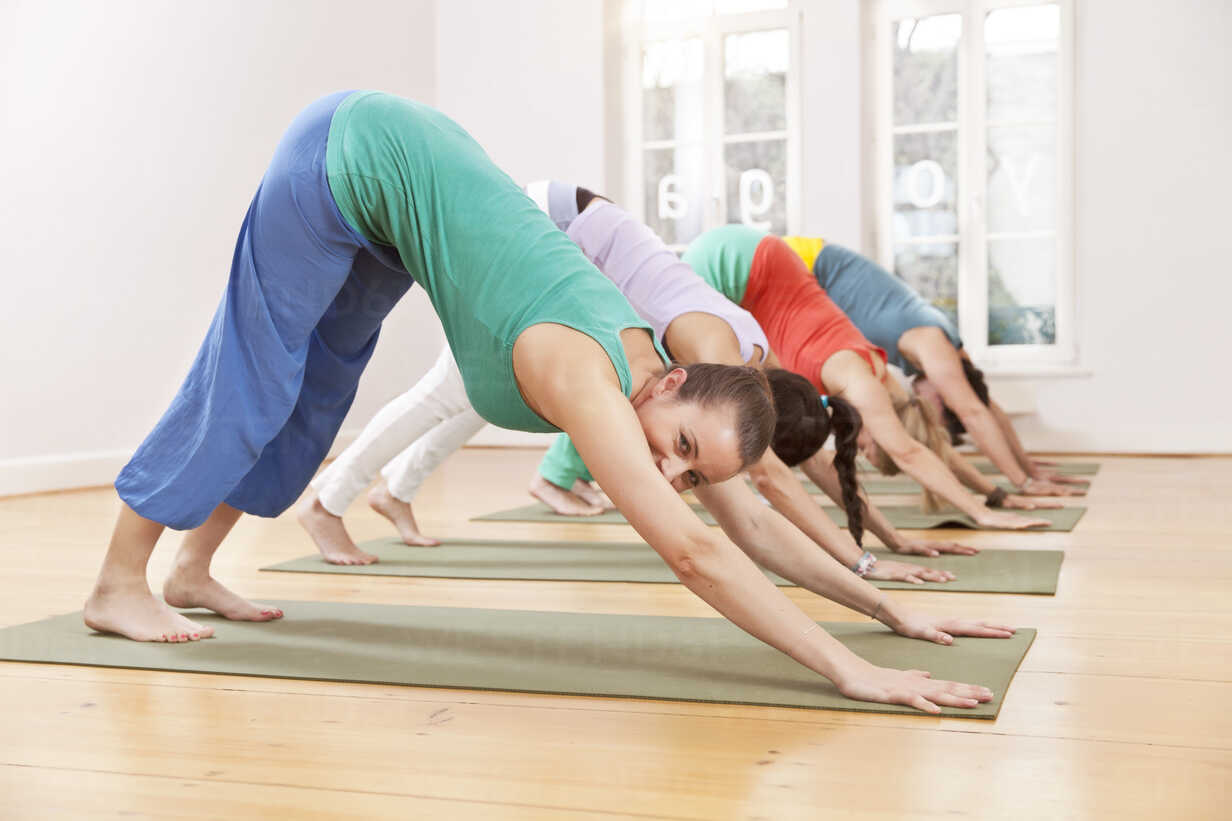 Group of people in yoga studio holding down dog pose – Stockphoto