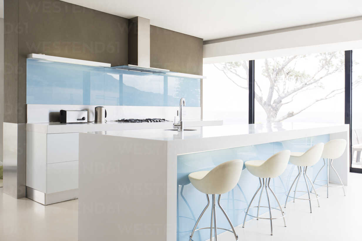 White and clean modern kitchen with stools at kitchen island ...